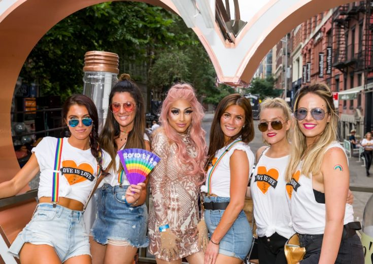 girls posing with drag queen on top of the tito's pride parade float