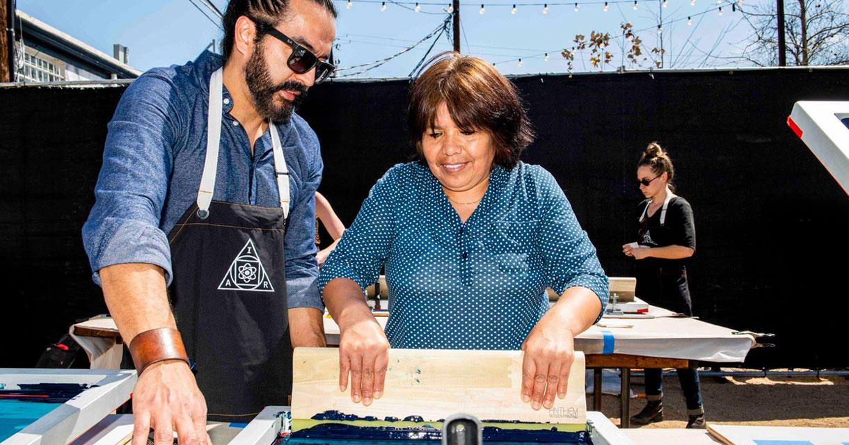 man and woman screen printing outside