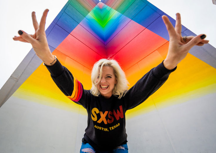 girl in an sxsw sweatshirt holding up peace signs in front of a rainbow background
