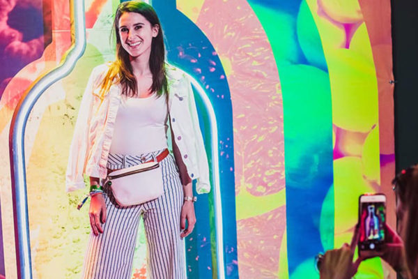 girl getting her photo taken in front of multicolored wall at coachella