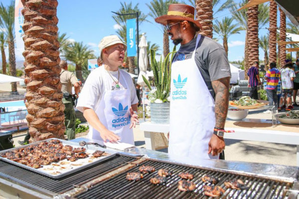 men in adidas sports club aprons grilling meat
