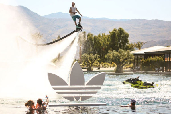 man on a hydro jet above a pool with an adidas sign