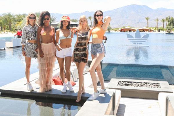 models standing by a pool with adidas sign