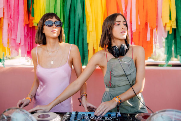 two women dj's standing in front of colorful streamers at an instagram coachella pop up experience