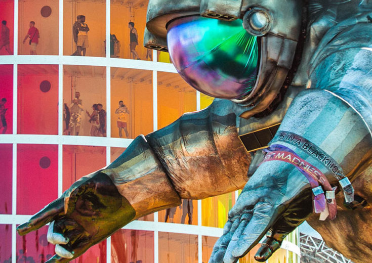 large astronut statue in front of a colorful building with people inside