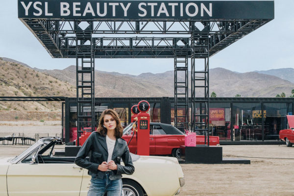 women in a leather jacket standing in front of cars at a YSL beauty gas station