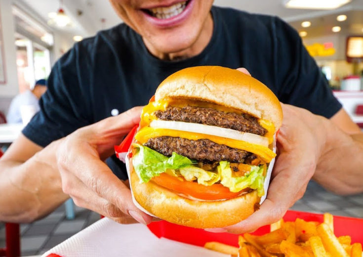 man holding an in n out double double