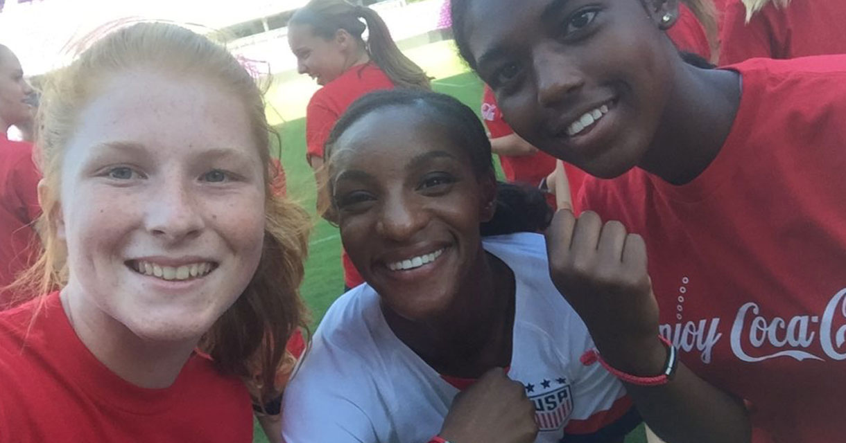 young girls posing with a member of the us women's soccer team