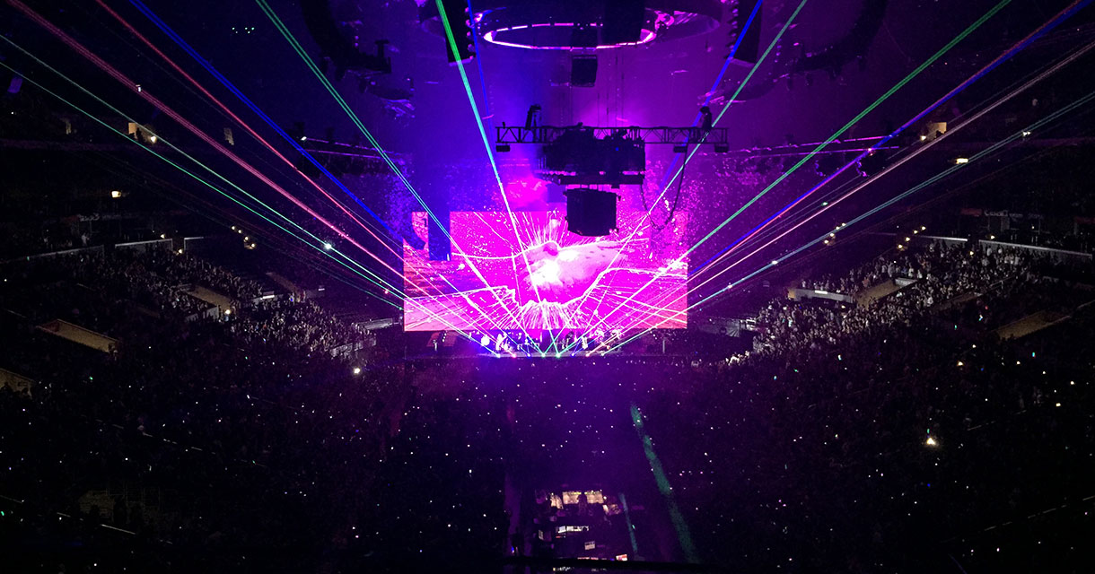 concert venue with a pink screen and bright lights