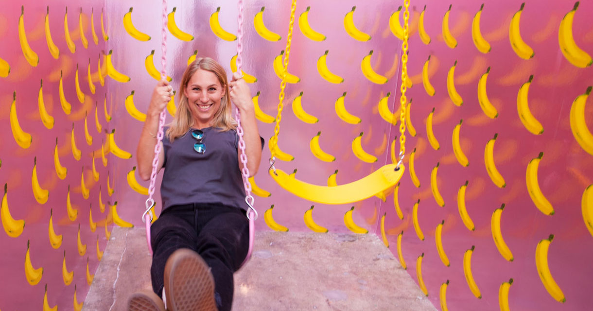 woman swinging on a banana swing in the ice cream museum