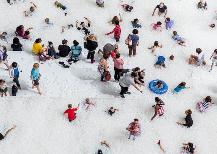 people playing in a large playpen of white balls