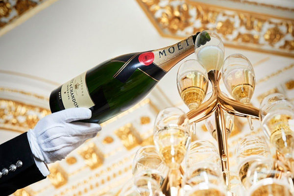 butler pouring moet champagne into a tower of glasses
