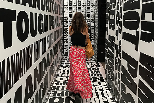 girl in red skirt walking through a tunnel printed with black and white words