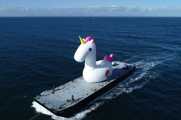 giant unicorn inflatable on a boat at sea