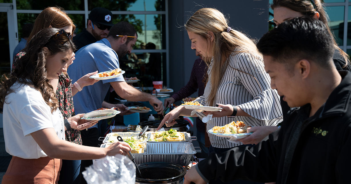fgpg employees serving themselves food at a company potluck