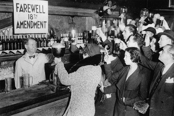 people cheer-sing in a bar with a farewell 18th amendment sign