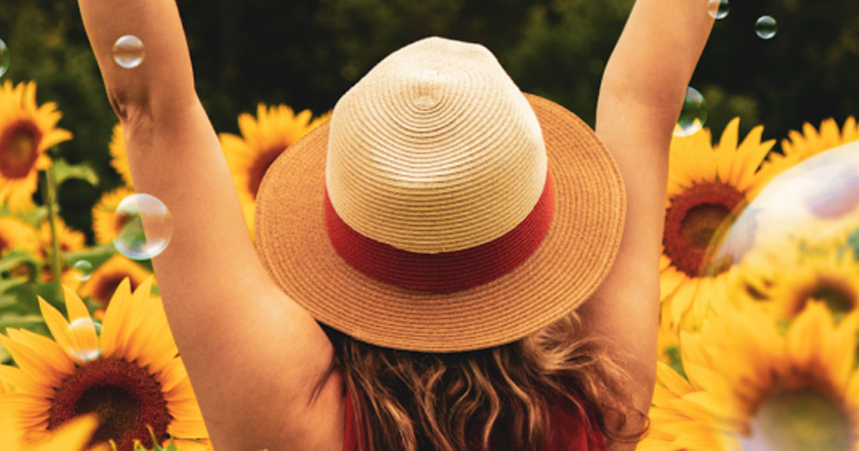girl in sunhat with surrounded by bubbles and sunflowers