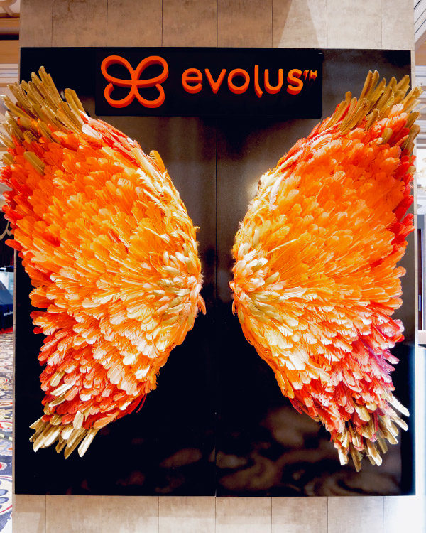 evolus brand activation trade show booth butterfly wings orange feathers fgpg experiential