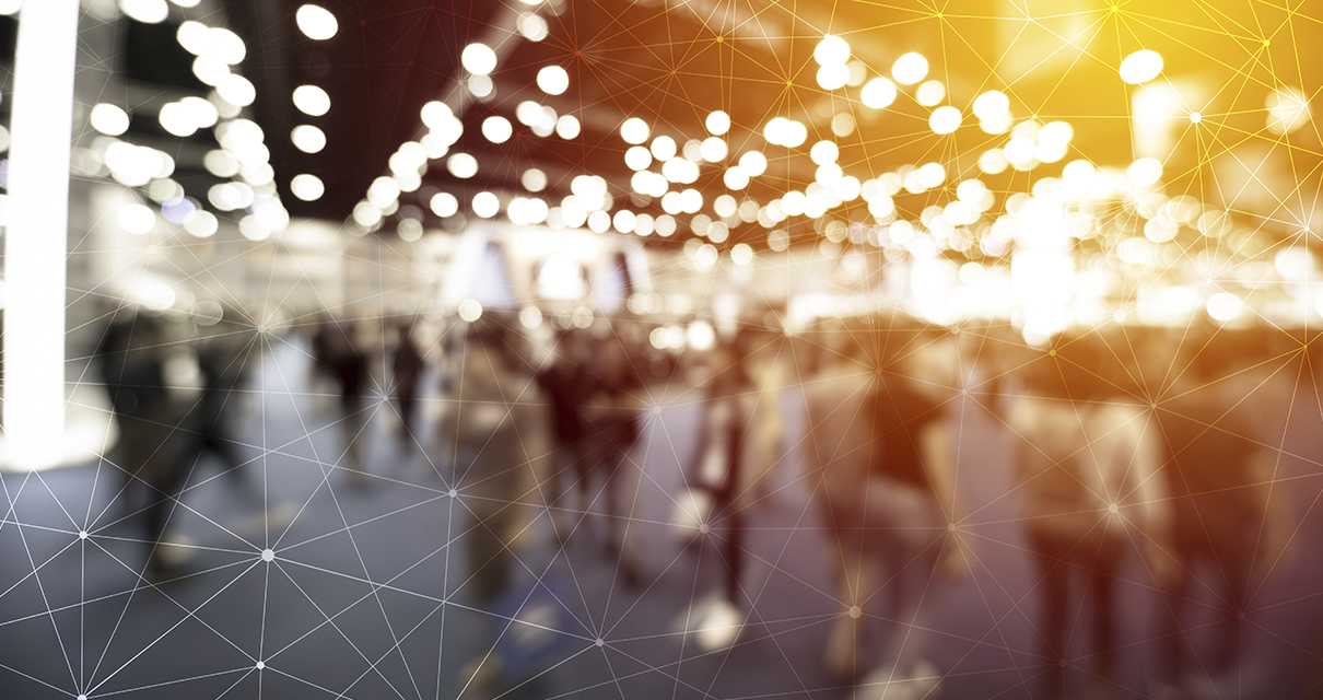 People attending a trade show, stylistically blurred with overlays of yellow lights and a white grid