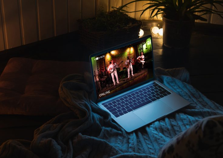 Laptop livestreaming a concert, sitting on top of a blanket in a cozy setting